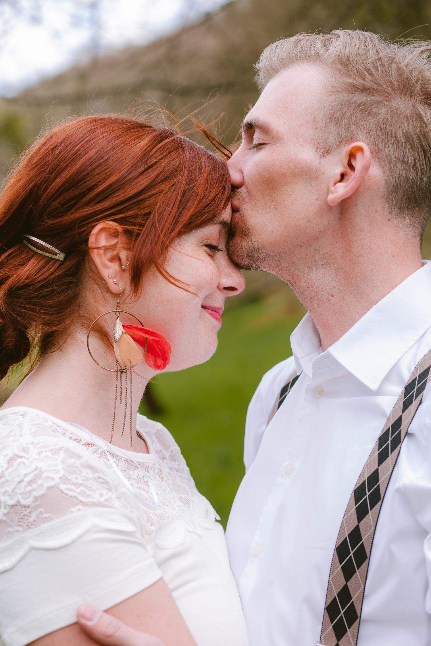 Mann mit Hosenträgern küsst Frau frontal auf die Stirn beim Verlobungsshooting in Trier