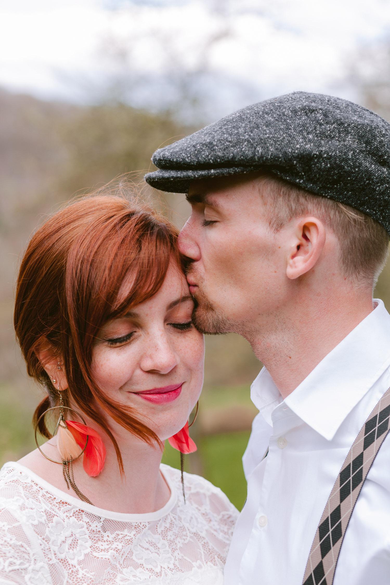 Mann mit Kappe küsst Frau seitlich auf die Schläfe. Frau trägt Federohrringe.