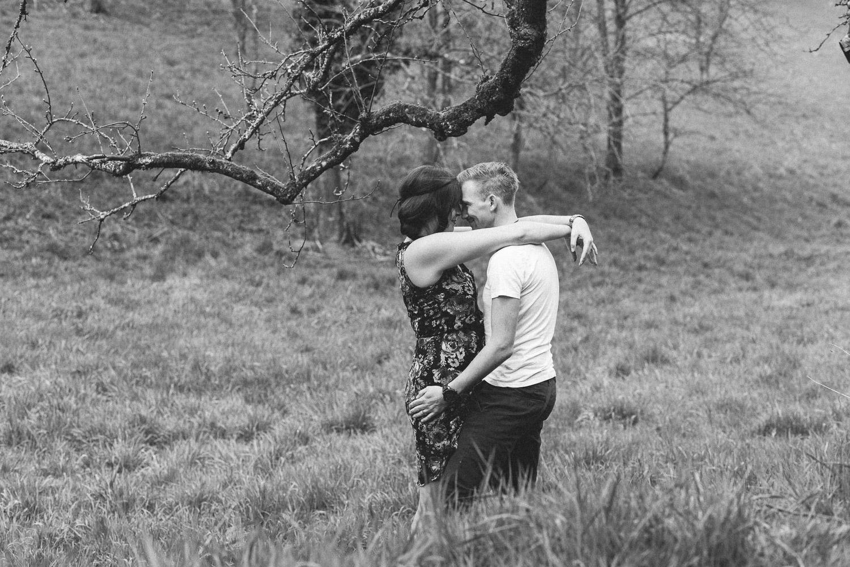 Umarmendes Paar auf einer Wiese in Trier unter einem Baum Verlobungsshooting Trier