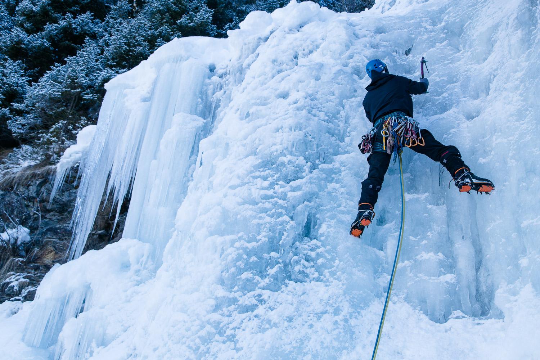Kletterer klettert einen Eisfall