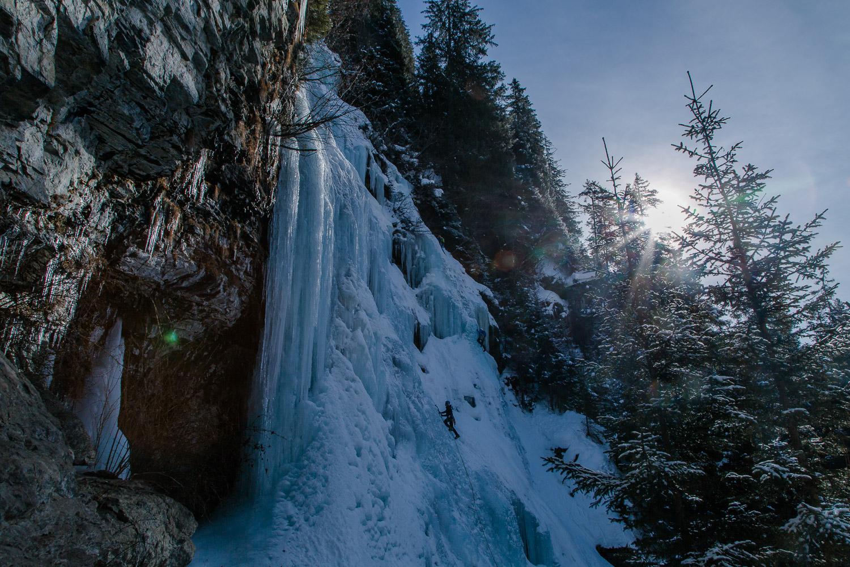 Gegenlicht Aufnahme eines Kletterers beim Eisklettern
