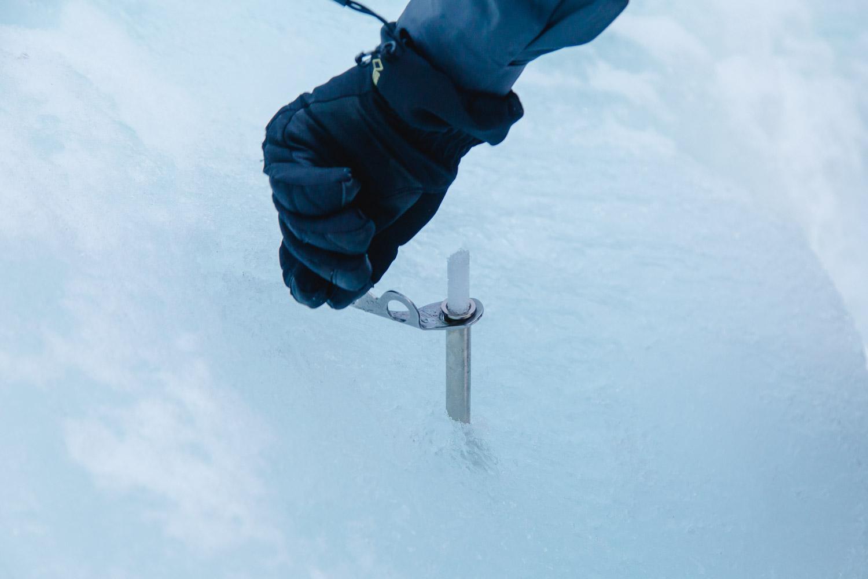 Hand mit Handschuh dreht eine Eisschraube ins Eis