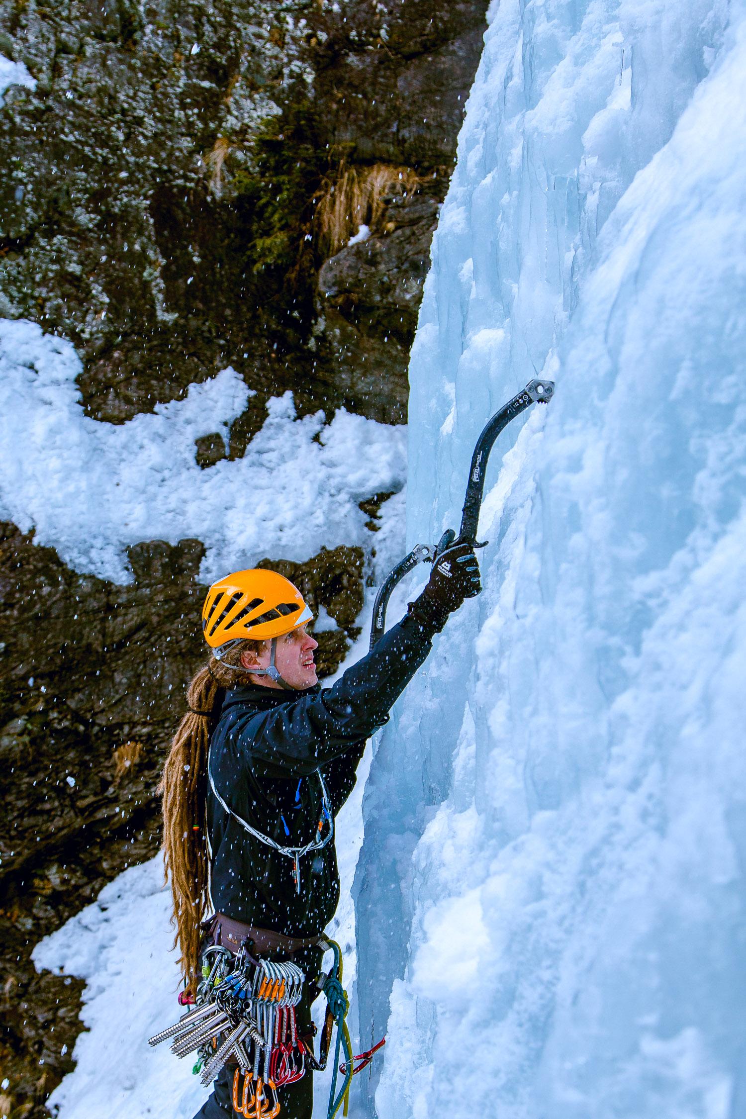 Nahaufnahme eines Eiskletterers, der einen Eispickel ins Eis haut