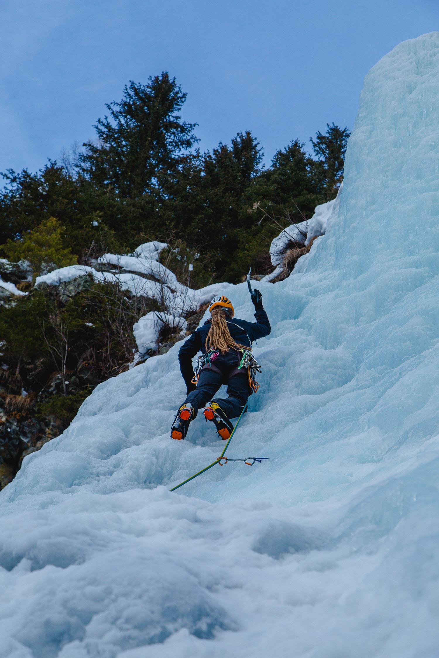 Eiskletterer haut Eispickel ins Eis