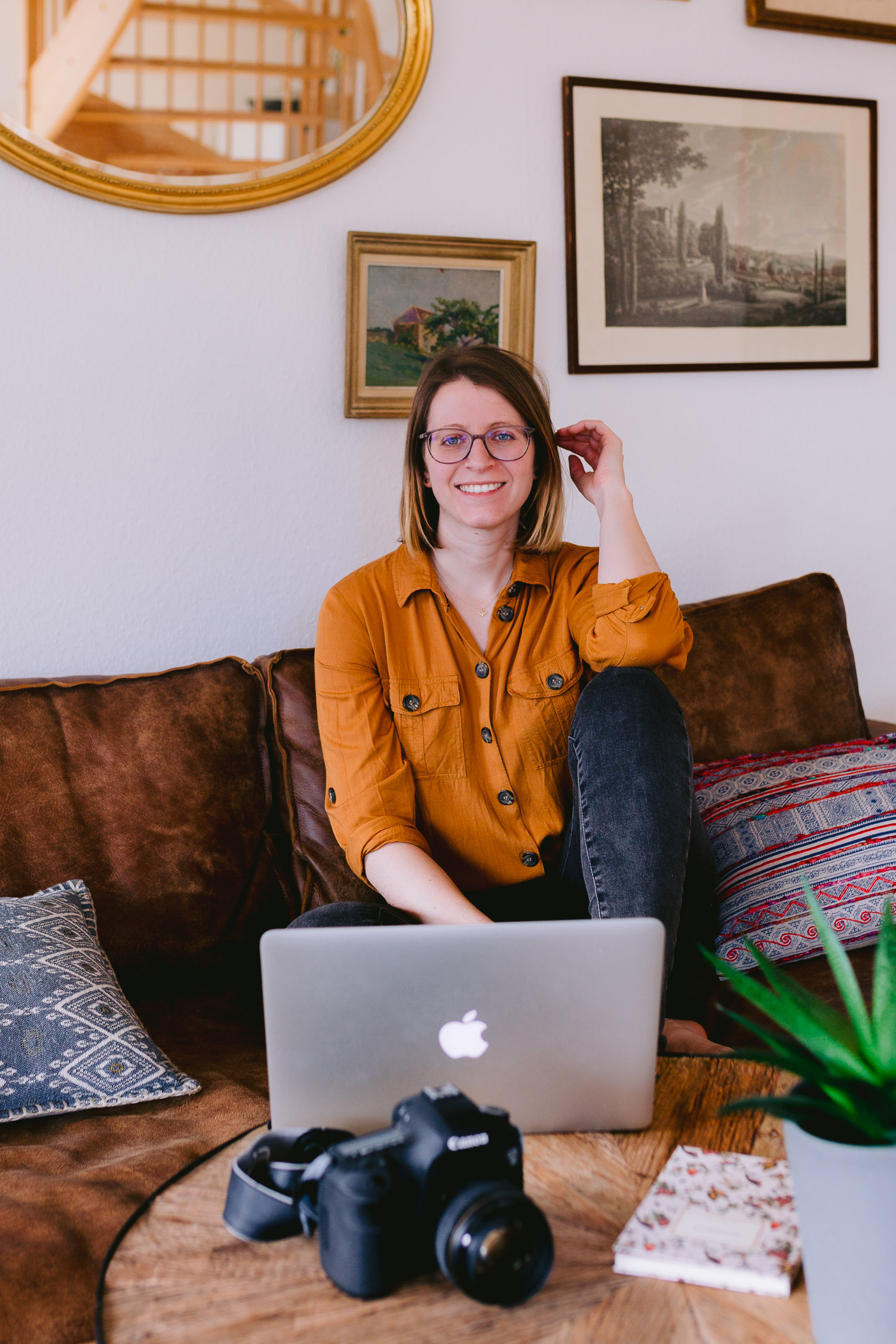 Portrait eines Fotografen sitzend auf der Couch beim Fotos bearbeiten