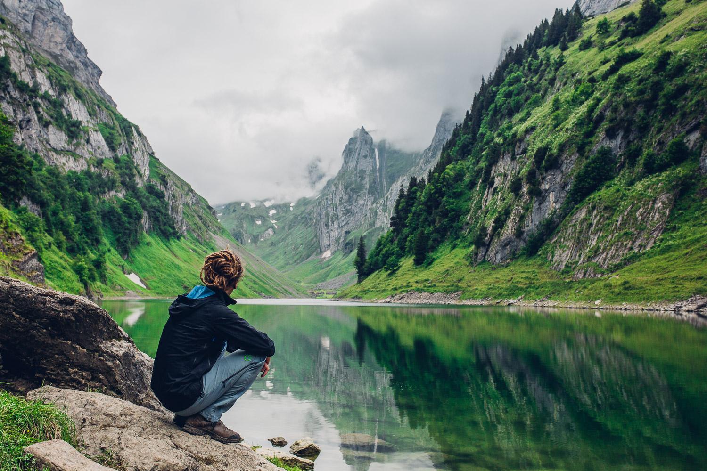 Wanderer sitzt am Fälensee im Alpstein der Schweiz und schaut auf das Wasser