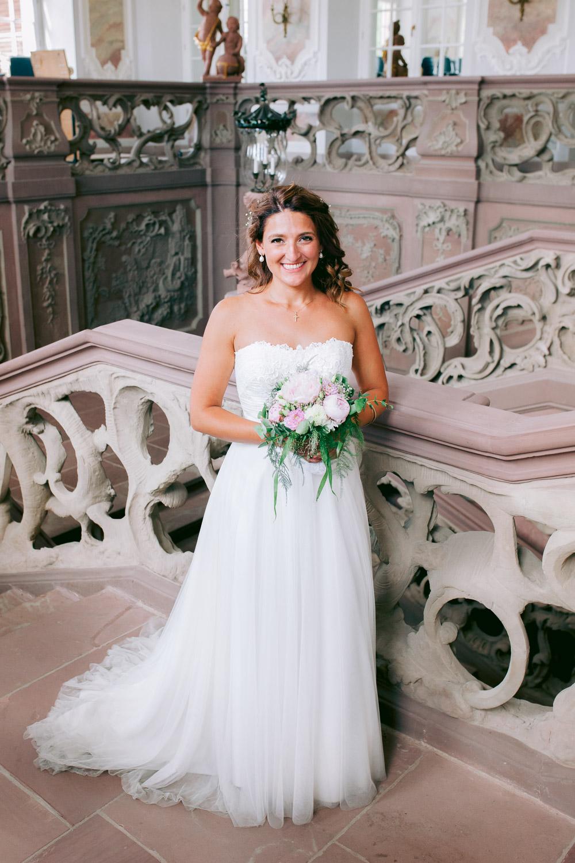Braut steht mit Brautstrauß im Kurfürstlichen Palais in Trier