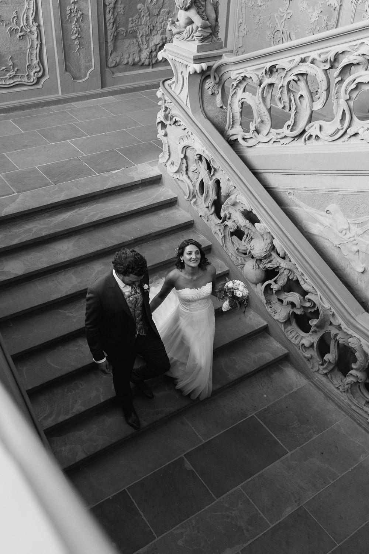 Brautpaar schreitet die Rokokotreppe im Kurfürstlichen Palais hinunter