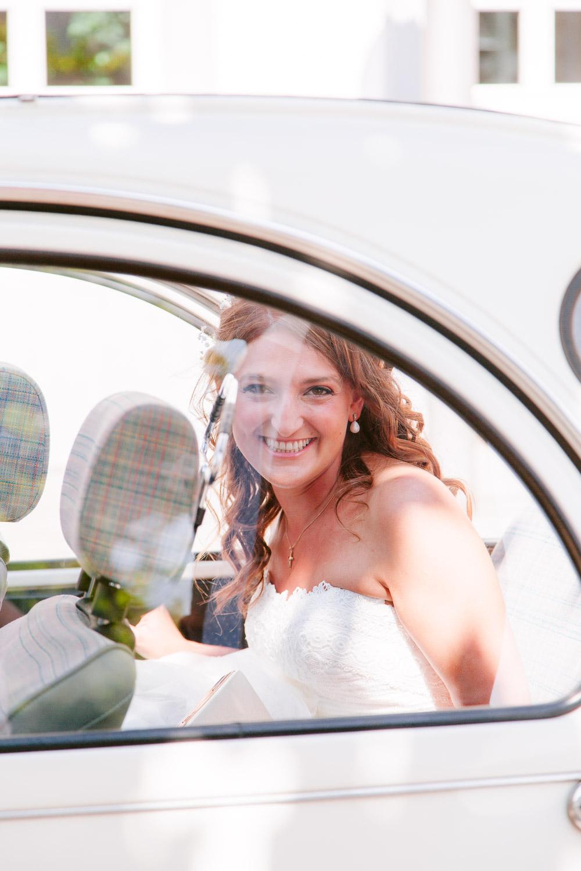 Braut lächelt aus dem Auto heraus