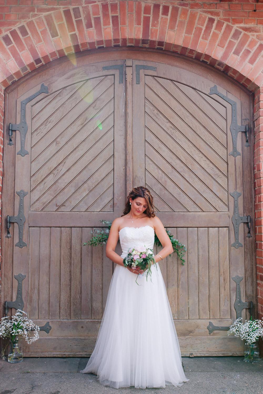 Braut steht vor Tor auf Gut Avelsbach