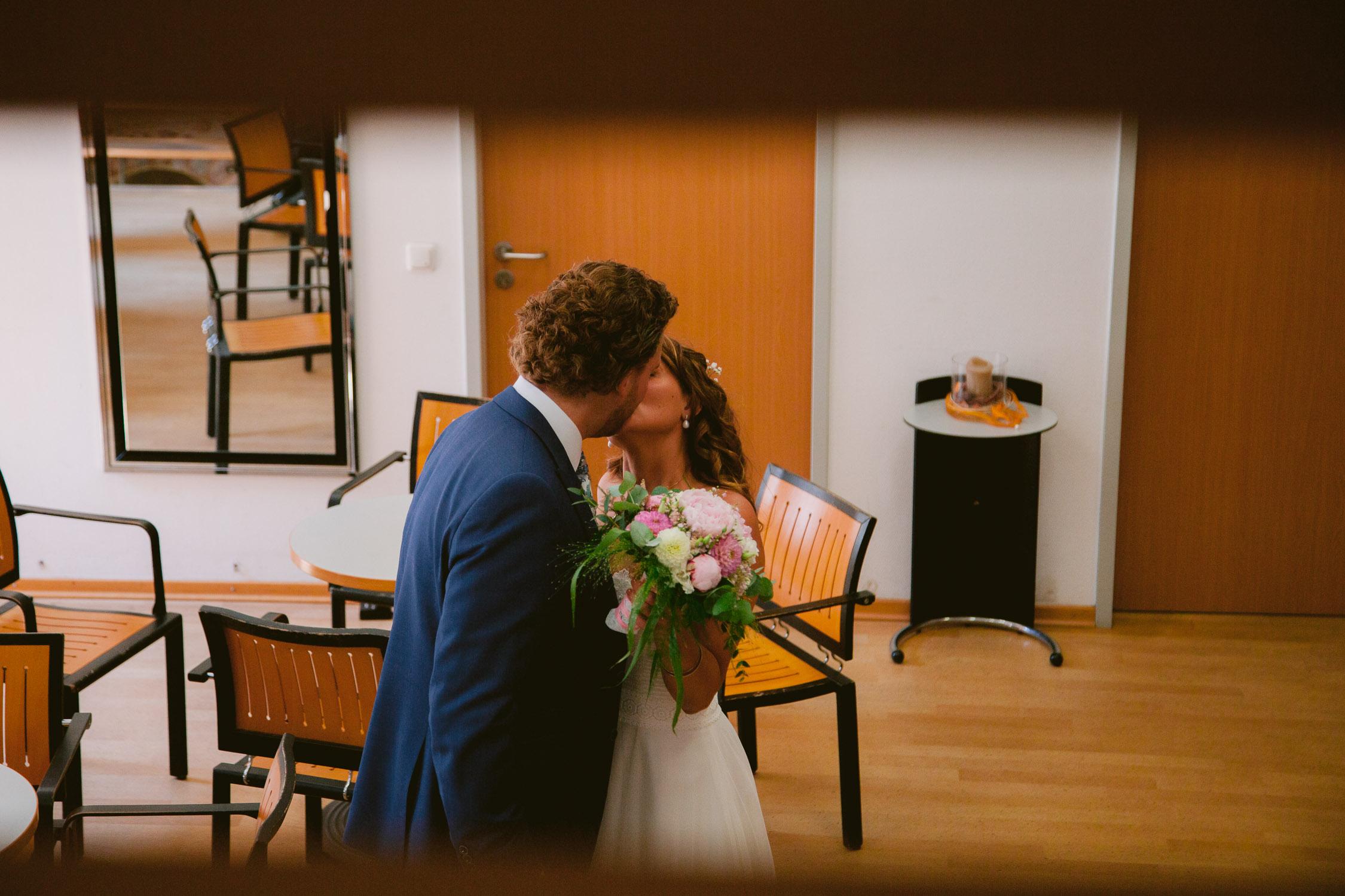 Brautpaar küsst sich im Wartebereich im Standesamt Trier