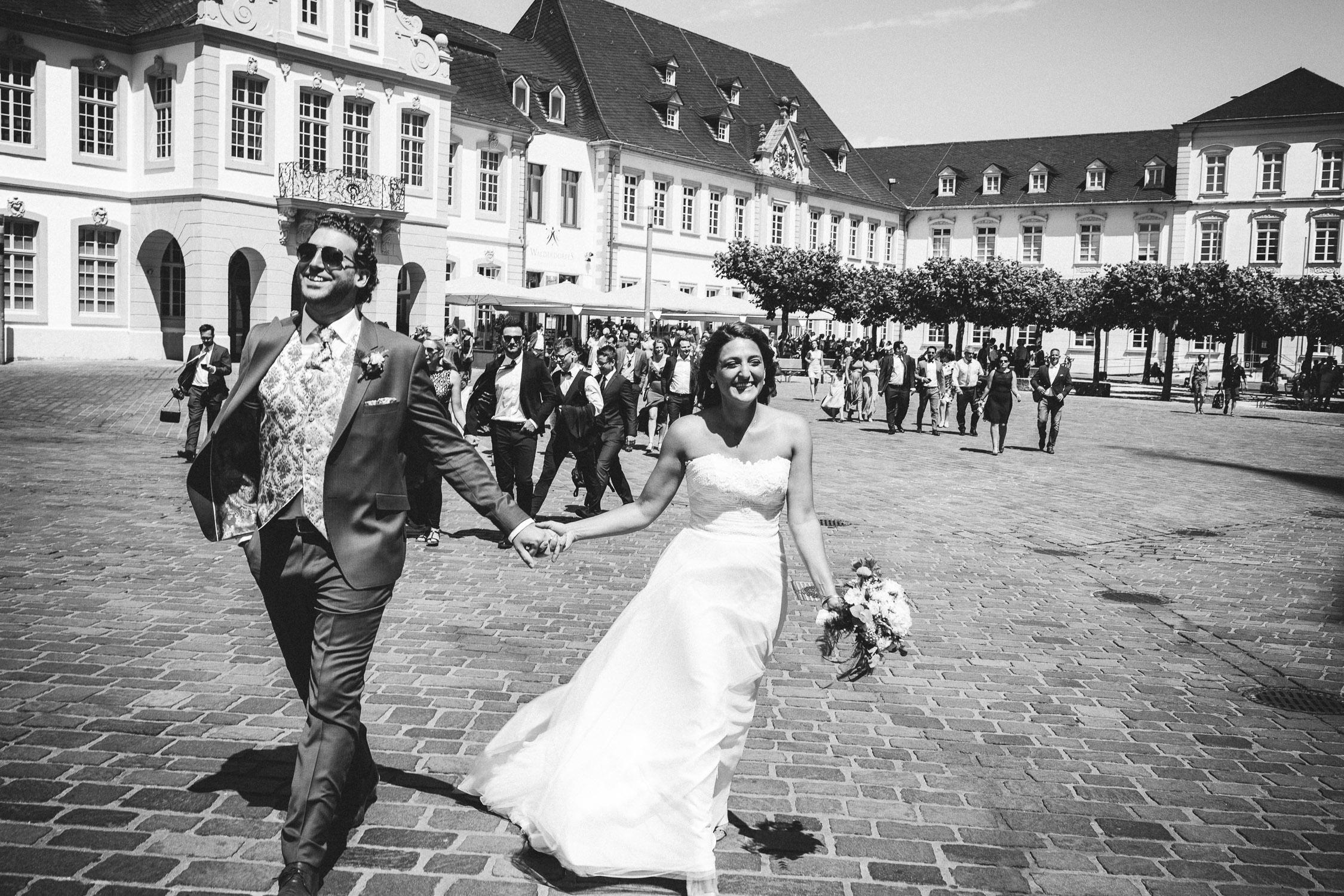 Das frisch vermählte Brautpaar geht über dem Domplatz in Trier Richtung Kurfürstliches Palais