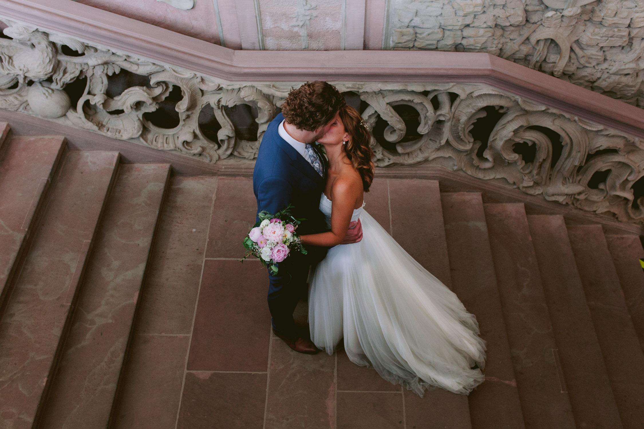 Brautpaar küsst sich auf der Rokokotreppe im Kurfürstlichen Palais in Trier