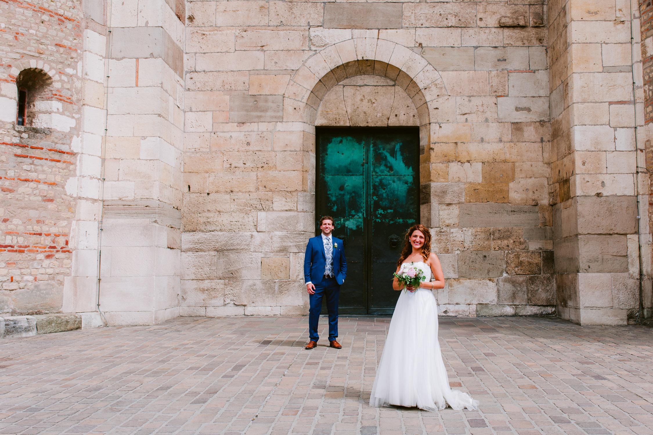 Brautpaar steht vor dem Tor des Trierer Doms