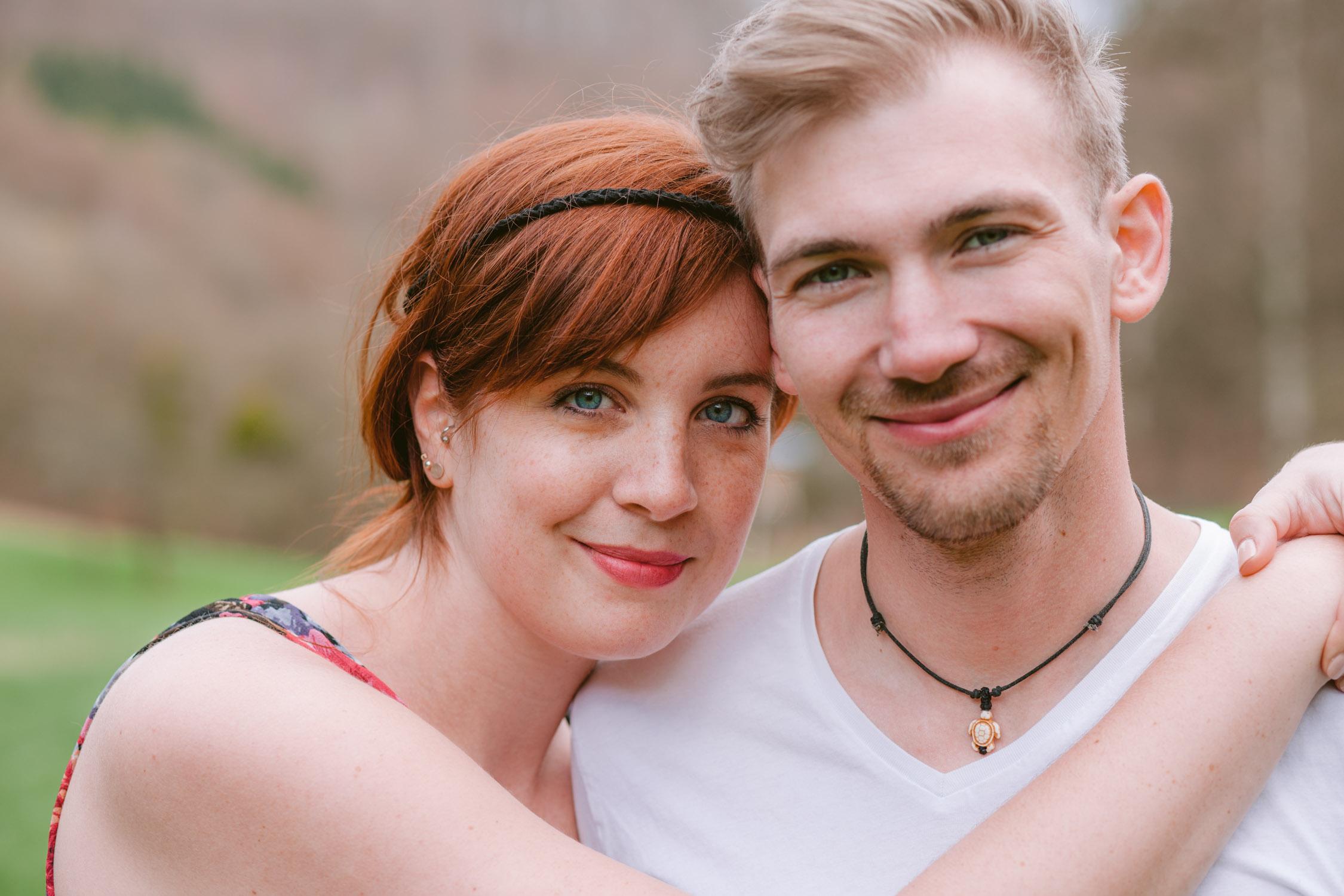Frau mit blauben Augen  und roten Haaren umarmt ihrem Verlobten Fotograf Trier