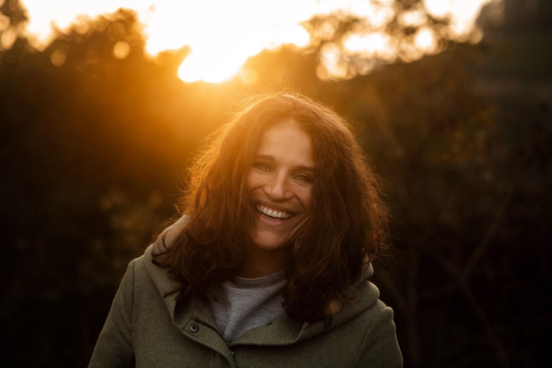 Lachende Frau hinter der die Sonne untergeht