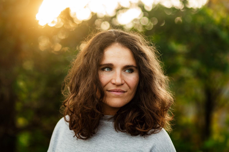 Portrait bei Sonnenuntergang einer Frau mit lockigem Haar
